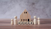 House words and wooden figures standing on wooden blocks consist of parents and children.Family together protection and safety Property and home insurance and managing real estate investment concept.