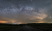 Suburban night highway, over the starry sky and the milky way