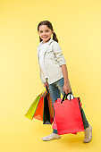 Back to school sales and deals. Back to school season great time to teach budgeting basics children. Girl carries shopping bags. Prepare for school season buy supplies stationery clothes in advance