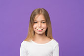 Girl with beautiful smile isolated on purple background. Child with cute face studio portrait. Model with shining blond hair and green eyes. Kid in white jumper having fun, happy childhood concept