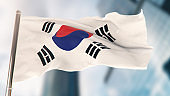 National Flag of South Korea Against Defocused City Buildings