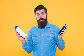 Which soap best. Bearded man hold soap bottles yellow background. Hipster choose liquid soap. For washing in bath or shower. Skincare and health. Grooming and hygiene. Soap cleanser for male skin