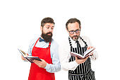 Some problems. Household duties. Cooking food recipes. How to cook. Men bearded hipster cook apron reading books about culinary. No idea how cook food. Culinary book concept. Men in charge household