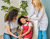 Child with her mother trying on a hearing aid by audiologist at a hearing clinic