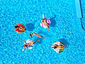 Aerial of hot pretty girls in bikini swimming in pool on floaties. Top view from above. Attractive fitted women in swimsuits relax sunbathing on inflatable flamingo, mattresses. Sunny day summer party