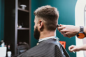 Close-up process male haircut, bearded man sitting in barbershop chair