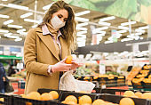 A woman in a medical mask and gloves choose oranges in the supermarket. Shopping during the coronavirus lockdown. Epidemic of Covid-19 Restriction Concept