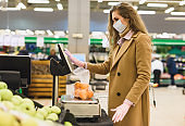 A woman in a medical mask and gloves choose and weighs oranges in the supermarket. Shopping during the coronavirus lockdown. Epidemic of Covid-19 Restriction Concept