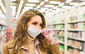Close up portrait of a young woman in a medical mask and disposable gloves in a supermarket. Shopping during the Covid-19 coronavirus epidemic
