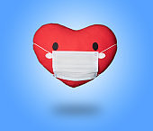 Fabric red heart with medical mask on blue background,Protection against virus, coronavirus.