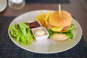 Large of tasty burger with beef, tomato, cheese and lettuce served in a plate
