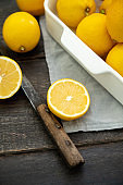 Ripe bright lemons in white bowl on the dark rustic background. Selective focus. Shallow depth of field
