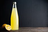 Traditional Italian lemon beverage limoncello in bottle on the dark rustic background. Selective focus.