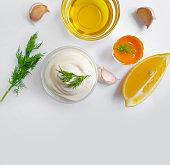 homemade mayonnaise,  eggs, lemon on white background
