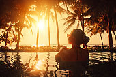 Vacation Beach Summer Holiday Concept. Silhouette beautiful woman relaxing in swimming pool on summer beach resort watching sunset.