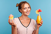 Young adult woman with pleasant appearance holding in hands delicious cake and fruit cocktail, looking at camera with happy facial expression.