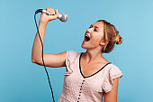 Side view positive blonde woman in summer dress loudly singing song, holding microphone in hand, having fun resting in karaoke, singer.