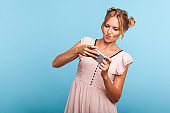 Portrait of adorable blonde female with two hair bundles using mobile phone with attentive focused expression, playing video game on cellphone.