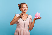 Happy smiling blond woman in summer dress holding piggy bank in hands and pointing to camera, satisfied with bank deposit, offering it to you.