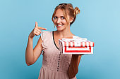 Cute smiling female with blonde hair in dress pointing at gift box and looking with happy expression to camera, showing awesome birthday present.