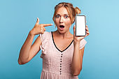 Advertisement of mobile device or application. Blonde astonished girl pointing at cell phone blank display, keeps mouth widely opened, shocking offers.
