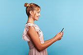 Profile of friendly lady with two hair buns in dress, making video call on mobile phone or broadcasting stream, using gadget for online communication.
