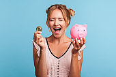 Excited pretty woman with blonde hair and wearing summer dress, yelling happily, holding piggy bank and gold crypto coin, growth bitcoin.