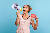 Profile of young adult woman promoter in dress announcing great news in megaphone holding card with sale inscription in hand, advertising discounts.
