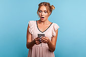 Astonished beautiful young adult woman in summer dress, using smartphone and watching shocking video, reading message with amazed expression.