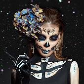 Halloween beauty skeleton woman makeup face Bokeh glitter. Girl death Halloween costume. Day of The Dead. Charming and dangerous Calavera Catrina