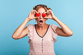 Surprised blonde woman with two funny hair buns in summer dress covering eyes with red hearts, hiding behind symbol of love, sees something astonished.