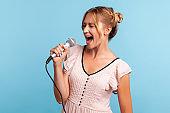 Profile of young adult female wearing summer dress singing loudly in karaoke, talented woman sings favorite song in microphone, keeps eyes closed.
