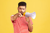 Displeased bossy man with beard in striped t-shirt pointing finger at camera holding loudspeaker near mouth, talking to you, protesting