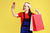Positive courier female with smile taking selfie or having video call while holding shopping bags.