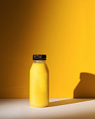 Smoothies of yellow color in a bottle on a yellow background with hard shadows. The concept of sports nutrition.