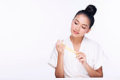 Beauty young woman doing manicure with cutting her fingernail while sitting over isolated white background with copy space. Healthy care concept.