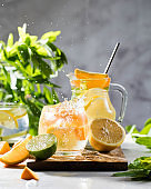 Refreshing lemonade with lemon and mint in a jug and glass with splashes. Summer drinks. Copy space.