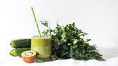Green smoothie in a glass with kiwi, cucumbers, parsley and dill. The concept of healthy eating. Copy space.