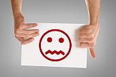 Two hands holding white sheet with sad face emoticon isolated