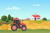 Harvesting in autumn landscape, modern farm tractor on wheat field with haystack, house