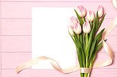 A bouquet of beautiful tulips and a gift on a wooden background top view.