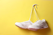 Modern trendy sneakers hang on laces on a colored background.