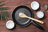 Coconut oil and a frying pan on a wooden table close-up.