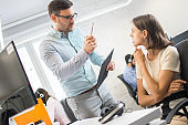 Male boss threatening with pen his female employe in the office.