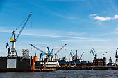 Container cranes and a battleship in Hamburg, Germany