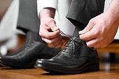 Man tying shoelaces on black shoes