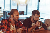 Young men in casual clothing enjoying beer