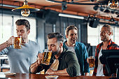 Group of handsome young men in casual clothing enjoying beer and communicating