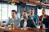 Cheering young men in casual clothing watching sport game and enjoying beer