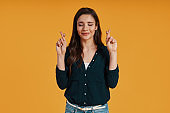 Attractive young woman in casual clothing crossbreeding fingers and smiling